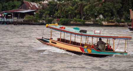 Thai motor boat float on Chao Phraya River. Tourists like to travel by boat to see Thai life on riverside. Stock Photo