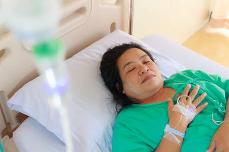 Close up of a woman patient in hospital with saline intravenous (iv) Imagens