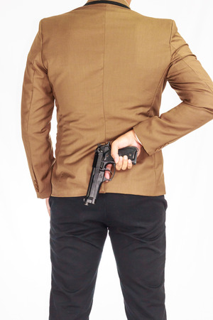 businessman hiding a weapon behind his back