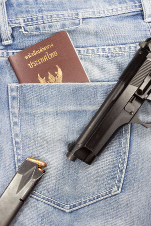 bullet proof: Thai passport and gun in jeans pocket