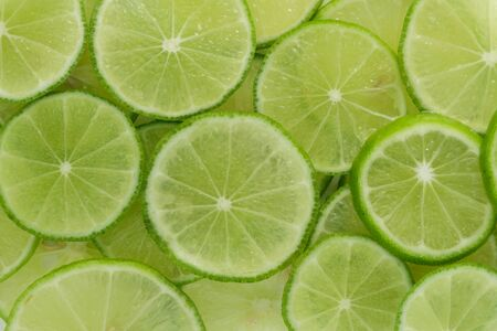 Green background with citrus-fruit of lime slices. Imagens