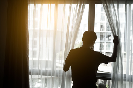Man in dark room opens curtains on window to the morning light.