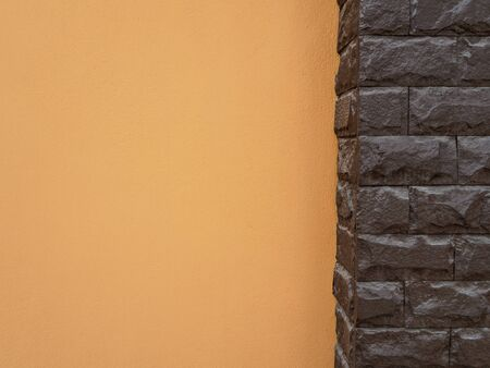 cement pole: Dark brown stone pole and orange cement wall, Copy space Stock Photo