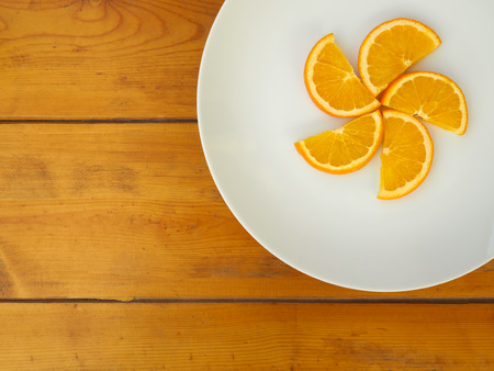 semicircle: Fresh semicircle oranges on white dish on wooden table