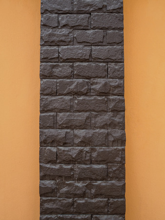cement pole: Dark brown stone pole and orange cement wall