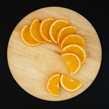 semicircle: Fresh semicircle slice orange on chopping wood isolate on black  background