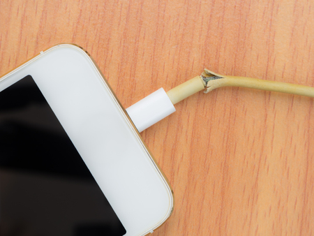 lacerate: Top view of broken charger cable with smart phoneon the wooden table Stock Photo