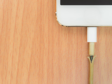 lacerate: Top view of broken charger cable with smart phone on the wooden table with copy space