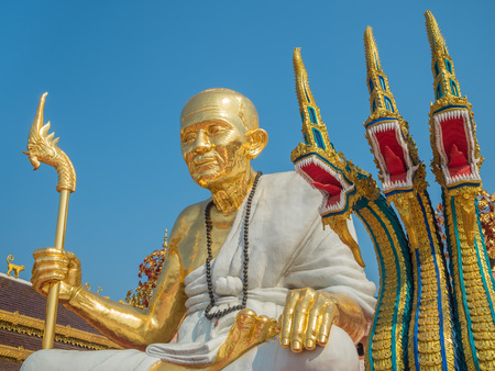monk robe: Big Golden Venerable Old Monk Statue in White Robe and Three Heads Serpent in Temple Names Wat Saeng Kaew Bodhi Yan at Chiang Rai, Thailand Stock Photo