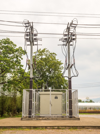 amp tower: Dangerous Electricity Substation and Twin High Voltage Pole Stock Photo
