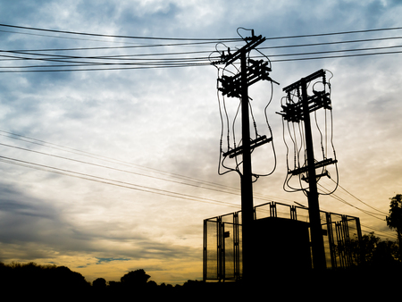amp tower: Silhouette of Electricity Substation and Twin High Voltage Pole with Two Tone Cloudy Sky Background