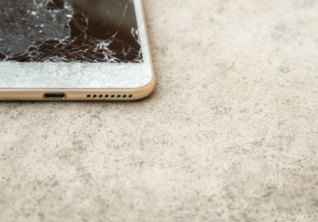 high key: Close up of broken mobile phone or tablet droped on cement floor with copy space, High key