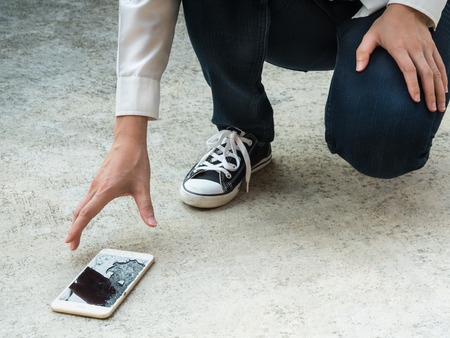 body parts cell phone: Person Picking Broken Smart Phone (Cracked Screen) of the Ground