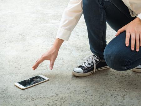 Person Kommissionierung Gebrochene intelligentes Telefon (Cracked Screen) des Boden Standard-Bild