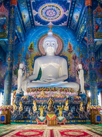 witness: Big white jade statue of the Buddha calling the earth to witness or earth touching Buddha and wonderful mural in blue chapel at the temple in Chiang-Rai, Thailand