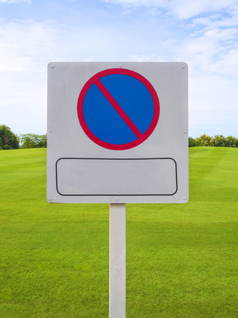 no parking sign: Road sign as No Parking sign on green field and beautiful sky background Stock Photo