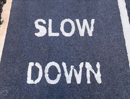 marking up: Close up of SLOW DOWN sign marking on bike lane, for warning the drivers and cyclist to reduce speed. Stock Photo