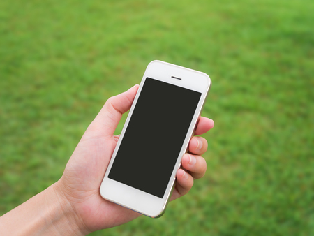 Human hand holding mobile phone against blurred green field background, Horizontal