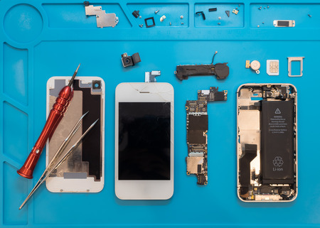 Flat lay image of dismantling the broken smart phone for preparing to repair or replace some components, Top view