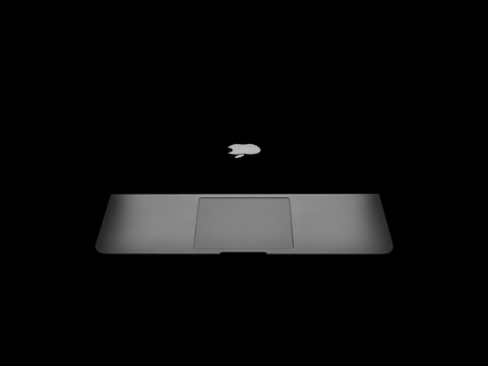 retina display: CHIANGRAI, THAILAND -OCTOBER 19, 2016: New Macbook Pro with Retina display showing backlight of Apples logo and trackpad in dark. MacBook is a brand of notebook computers manufactured by Apple Inc.