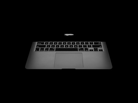 retina display: CHIANGRAI, THAILAND -OCTOBER 19, 2016: New Macbook Pro with Retina display showing backlight of Apples logo and keyboard in dark. MacBook is a brand of notebook computers manufactured by Apple Inc.