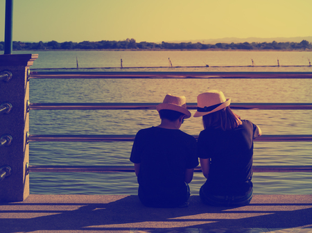 Backside of lovers in same groomed sitting on pier and looking at the river in evening, Vintage style, Cross process filter