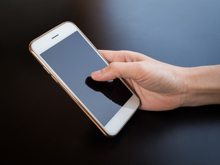 mobile phone screen: Close-up image of one hand person holding and using smartphone on black table Stock Photo