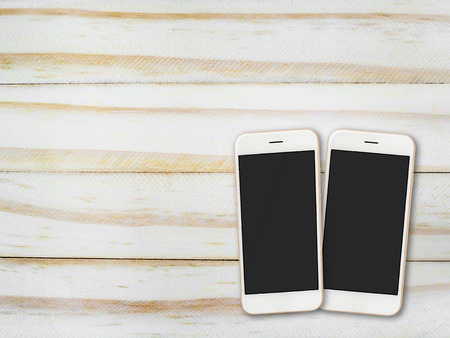 Top view (Flat lay) image of two blank screen smartphone on wooden background with copy space