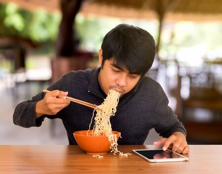 piggish: Man eating chinese noodle monstrously whilst looking and using tablet. Concept of smartphone addiction, phubbing or social network issues