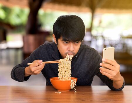 piggish: Man eating chinese noodle monstrously whilst looking and using smartphone. Concept of smartphone addiction, phubbing or social network issues  Stock Photo
