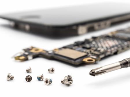 Close-upbeeld van schroef en schroevedraaier met vage smartphonecomponenten op witte achtergrond