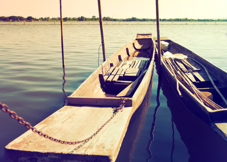 two tone: Two old wooden boats are close docked to river side, Vintage color filter style
