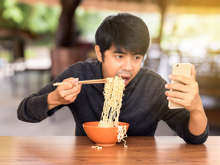 piggish: Man eating chinese noodle monstrously whilst looking and using smartphone. Concept of smartphone addiction, phubbing or social network issues