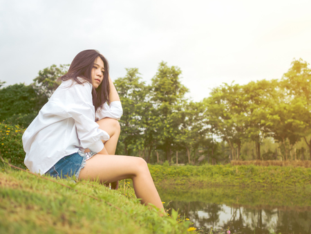 Portrait image of beautiful teenager girl loneliness in nature garden. Fashion sexy woman in white shirt and denim shorts jeans with copy space