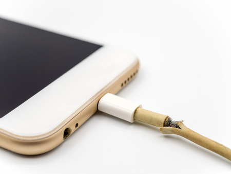 Close-up image of damaged charger cable connecting with smartphone on white background