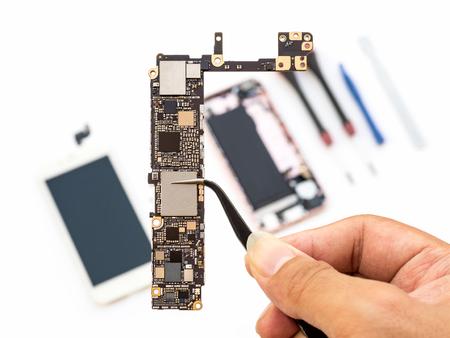 Close-up van de klembord van de technicushand klemmende logica op vage smartphonecomponentachtergrond Stockfoto