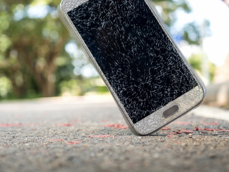 Close-up and motion blur image of old broken and cracked screen smartphone drop down on the floor with copy space