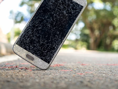 Close-up image of old broken and cracked screen smartphone drop down on the floor with copy space