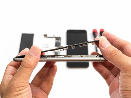 Close-up van technicushand die het gebarsten smartphonescherm op de vage achtergrond van de smartphonecomponent opstijgen Stockfoto