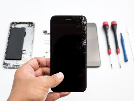 Close-up of cracked smartphone screen in technician hand on blurred smartphone component background