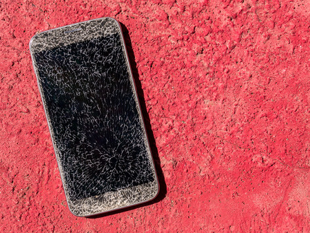 Top view and close-up image of old broken and cracked screen smartphone drop down on the red floor background with copy space