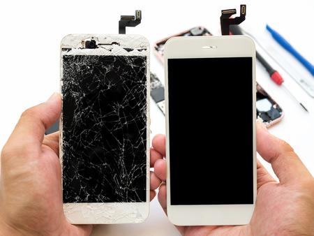 Nahaufnahme des gebrochenen Smartphoneschirms vergleichen mit neuem Schirm in der Technikerhand auf unscharfem Smartphonekomponentenhintergrund