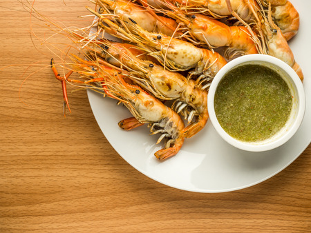 Top view image of Grilled shrimps with Thai culture seafood sauce on wood texture table with copy space