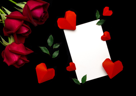 Top view (flat lay) image of white paper note, red rose, green leaf, red origami paper heart on black baclground. Valentines day concept