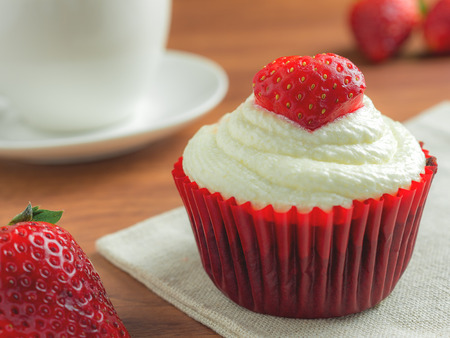 Close-up image of red velvet strawberry cup cake on coffee cup background with copy space, Valentine concept