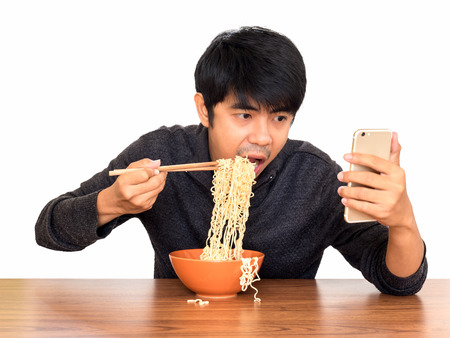 Man eating chinese noodle monstrously whilst looking and using smartphone isolate on white background  . Concept of smartphone addiction, phubbing or social network issues Stock Photo