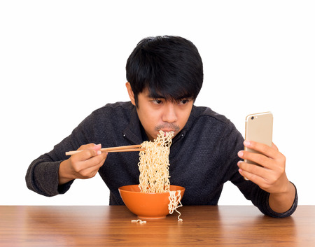 Man eating chinese noodle monstrously whilst looking and using smartphone isolate on white background with clipping path. Concept of smartphone addiction, phubbing or social network issues
