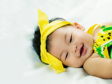 Portrait of cute short hair asia baby girl relaxing smiling or laughing and lying on her bed in color full wearing