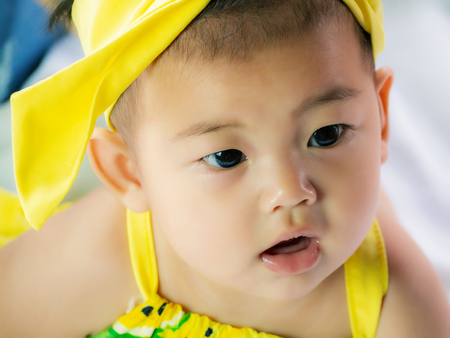 Portrait of cute short hair asia baby girl in color full wearing frowned and look something
