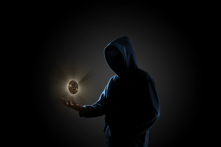 Golden Bitcoin floating above of hacker's hand in dark background. Finance, business, e-commerce or cyber crime concept 版權商用圖片